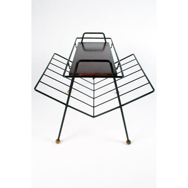 A multifuntional magazine stand in a wrought iron frame with wooden ball feet that holds a removable tray with wrought...