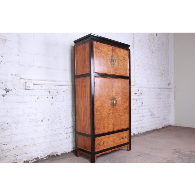 Offering a gorgeous Hollywood Regency Chinoiserie black lacquered and burl wood armoire dresser by Century Furniture. The...