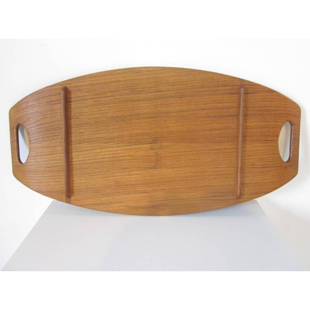 A large teakwood serving tray with side rail and leg rail design, two cut-out handles one of Quistgaard's most noted...