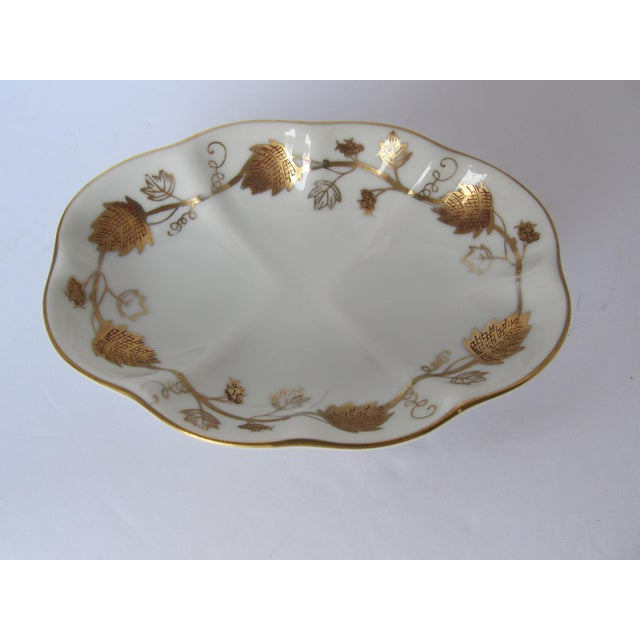 Add a little elegance to your bathroom with this vintage white porcelain soap dish with gold leaves and accents.