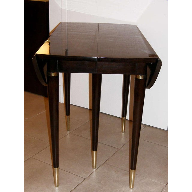 An ebonized walnut drop-leaf table with brass feet, by John Widdicomb, American C.1960's - with original label - the table...