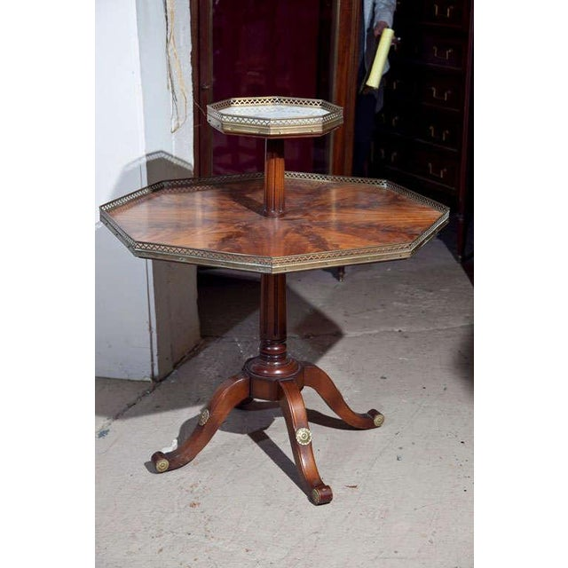 Jansen two-tier, octagonal table with a white marble top supported by a quad pod pedestal base. Both shelves with pierced...