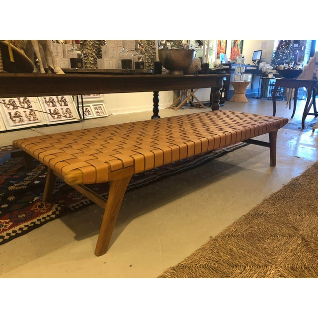 Mid-century style unique woven leather bench with light wood frame and boomerang legs.