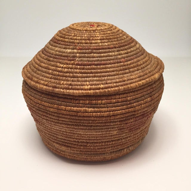 Beautifully proportioned and in excellent condition, this is a very fine Northwest Coast Salish tightly coiled lidded...