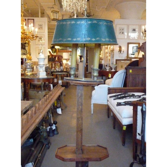 An unusual adjustable wooden floor lamp with a green tole shade.