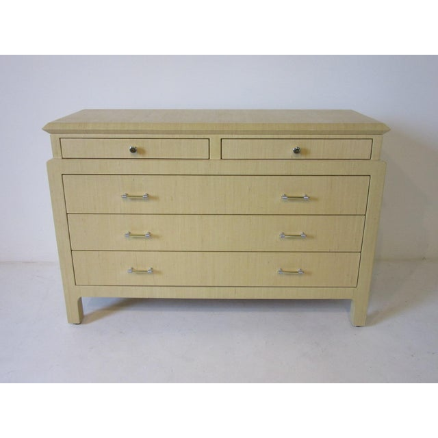 A five drawer linen wrapped chest in the manner of Karl Springer with two smaller upper drawers with brass and chrome...