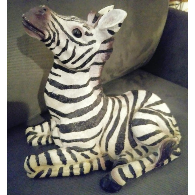 A sweet whimsical sitting black and white zebra statue. The statue is made of some sort of resin material. He has the...