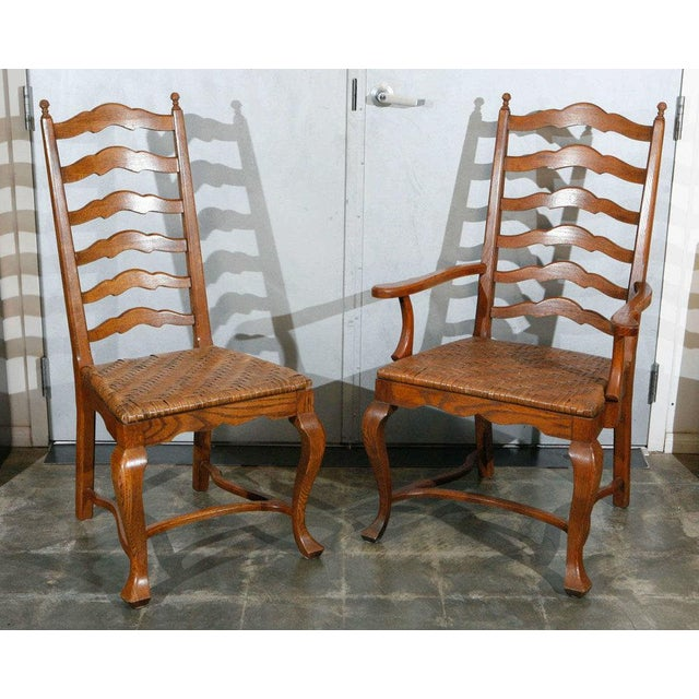 This charming set of dining chairs with: out turned legs, shaped stretchers, woven split oak seats, and tall ladder backs....