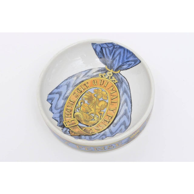 This bowl or dish by Piero Fornasetti and is of the period. It is all in Italian with a warrior crest outlined with a...