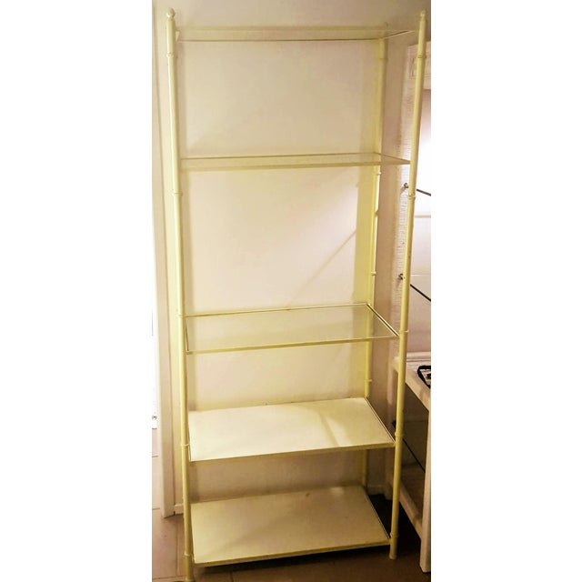 Mid-Century metal rectangular shaped etagere that has been fully painted in a glossy yellow canary paint. This Hollywood...