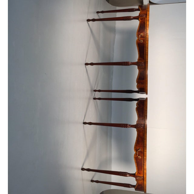A pair of elegant flame mahogany and satinwood demi lune consoles by Maitland Smith. English Adam style with graceful...