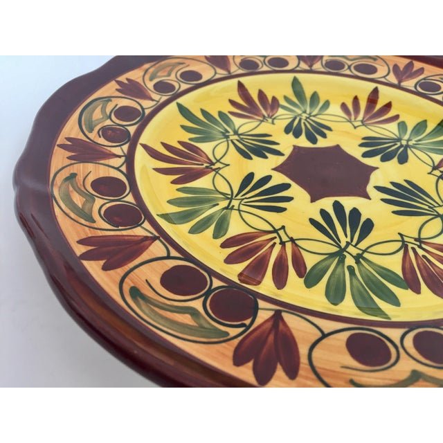 Polychrome hand painted and handcrafted ceramic wall decorative plate with polychrome floral design. It has a beautifully...