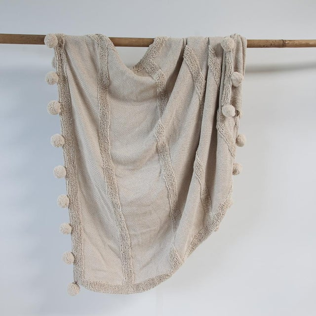 This on trend Zenza Boho Nomad Woven Cotton Throw in Cream, Ivory and Silver has well placed pom-poms for added detail....