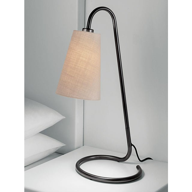 Black bronze tubular metalwork lamp with an elliptical base and an upright angled column. The base has rubber feet. The...