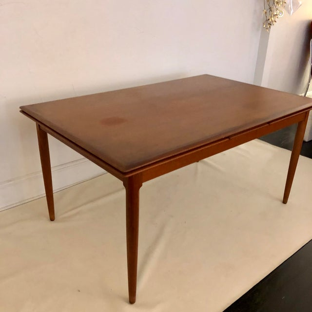 Beautiful solid teak dining table with large slide out extensions on each end. Comfortably seats 10 when fully extended!...