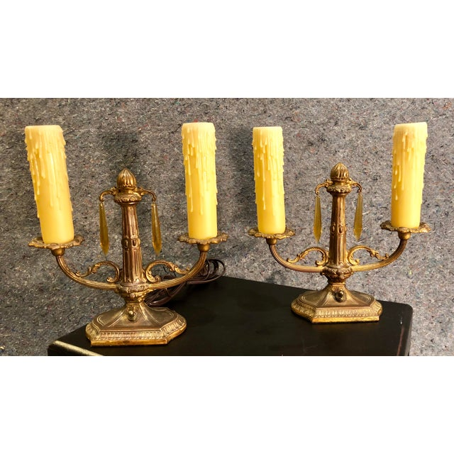 A vintage pair of gilded metal two arm lamps with honey resin candle sleeves and amber prisms. They measure approximately...