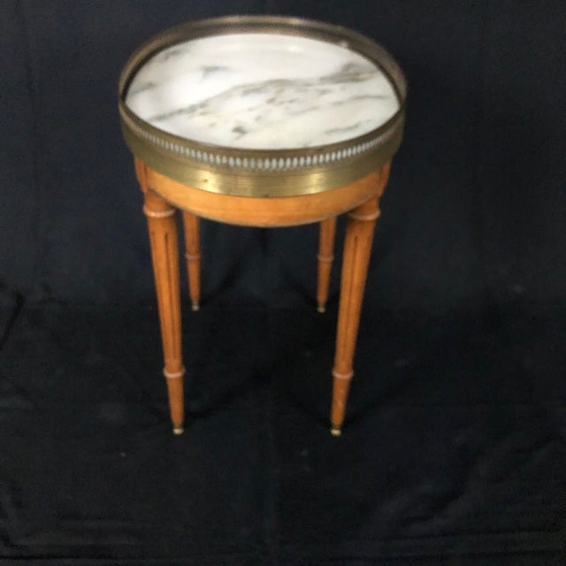 French Louis XVI style light oak side table having beautiful carrara marble top and brass gallery over reeded tapered legs...