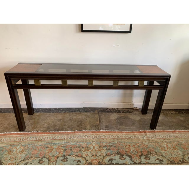 Contemporary Asian inspired mixed wood console with glass top. Dark wood stained frame & legs paired with burlwood and...