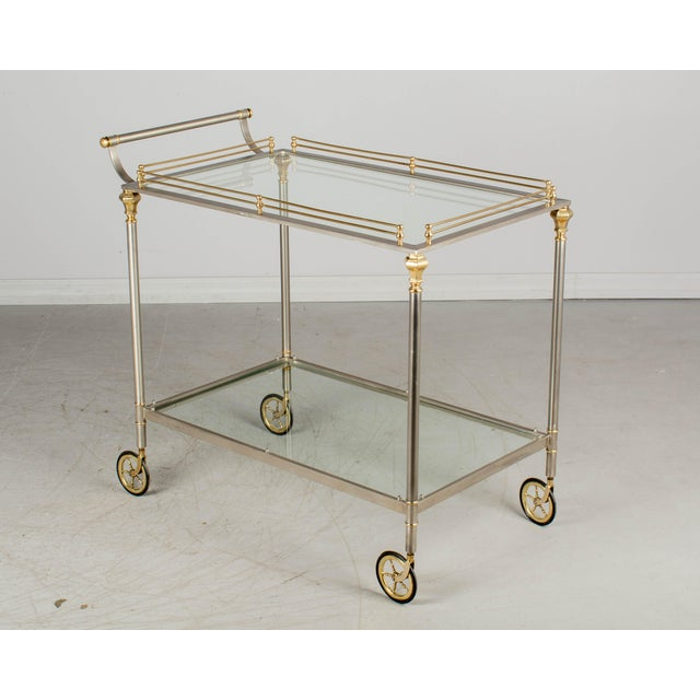 An Italian two-tier brushed nickel and brass bar cart in the style of Maison Jansen. Polished brass gallery, accent...