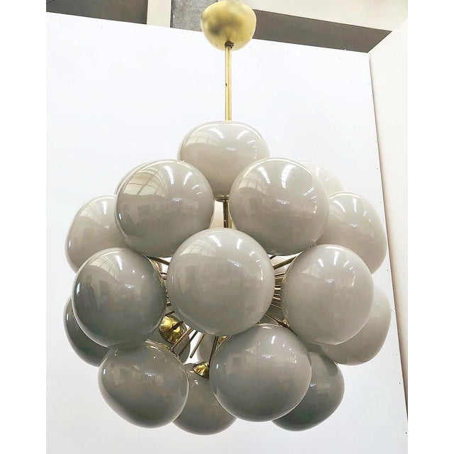 Italian chandelier with 24 light gray Murano pebble shaped glasses mounted on natural brass frame / Designed by Fabio...