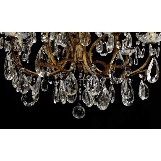 Antique Italian gilt metal and crystal twelve-light chandelier, foliated standard with scrolling arms, accented by crystal...
