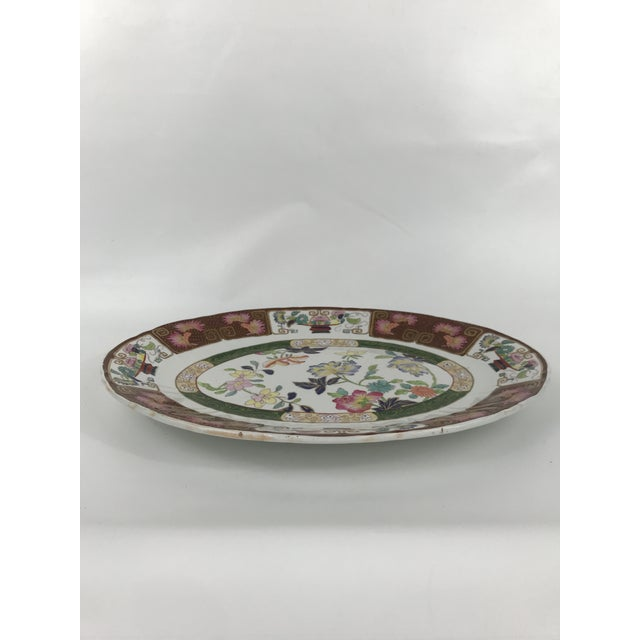 An oval shaped ironstone china platter by Ashworth with gilt and polychrome Imari style floral decoration.
