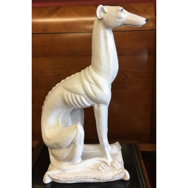This noble hound, seated on a pillow as befits her role of guardian mascot of a stately home, is made of white glazed...