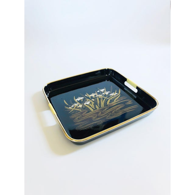 A wonderful square Mid Century tray made of molded black plastic. A centered floral design in gold and white has been...