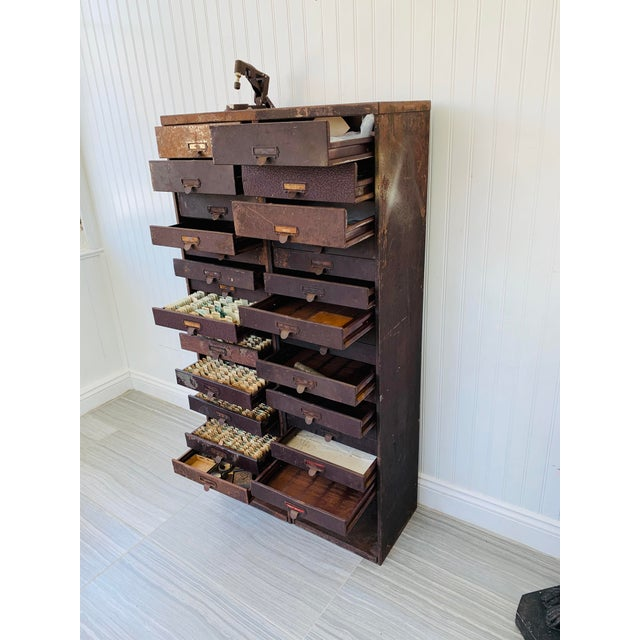 Two industrial metal flat file skinny drawer watchmaker / Jeweler parts cabinets with supplies! One has a foot-powered...