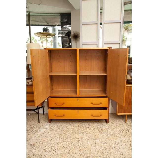 A large Jacques Adnet cherry cabinet with oak interior, cast brass hardware, and leather covered steel legs and trim,...