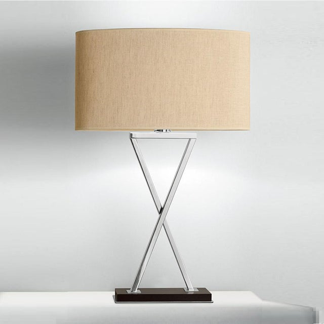 Polished chrome table lamp on chocolate colored wood base. The crossover sections pass one in front of the other and the...