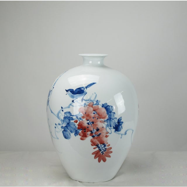 This blue & white with red flower porcelain vase was designed and made by Mr. Zhou, an artisan from Jingdezhen, an ancient...