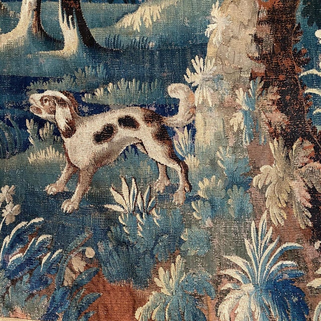 A fine Flemish pictorial tapestry depicting a lush forest backdrop with a dog in the foreground. The tapestry with a...