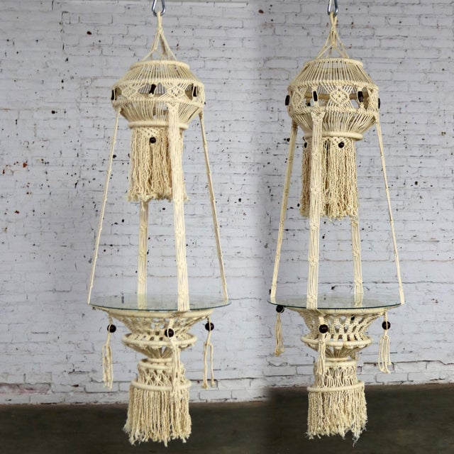 Beautiful pair of white cord macramé hanging tables with round glass tops. They are in wonderful age appropriate condition...