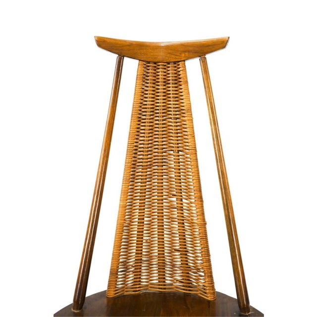 A showstopping solid, '60s-era, walnut and woven cane rocking chair designed by Arthur Umanoff for WASHINGTON WOODCRAFT of...