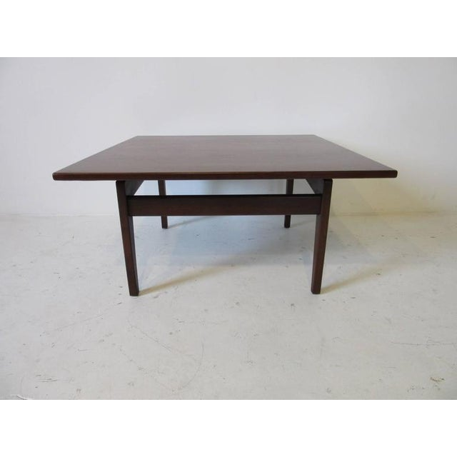A Danish styled dark walnut floating top coffee table with straight stretchers and winged stretchers, retains the...