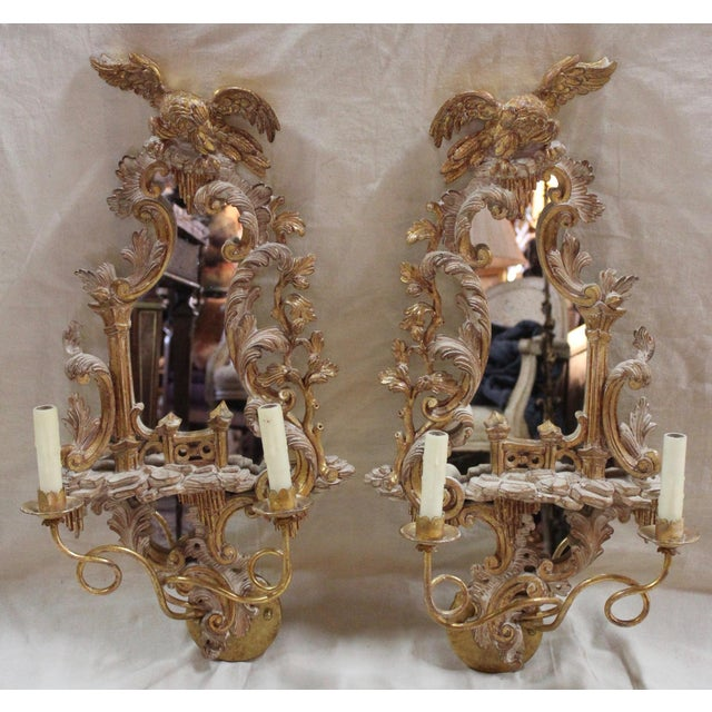 Pair of mirrored and carved wood two light sconces with wax candle sleeves, hard-wired, sold by New Metal Crafts,...