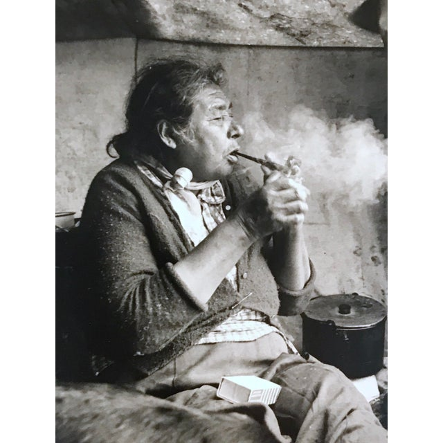 """""""Canadian Cree Woman Lights Her Pipe In Her Summer Camp"""" Vintage photograph showing a Cree woman exhaling a cloud of smoke..."""