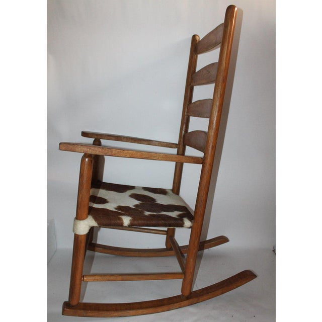 This fun and folky mid western ladder back rocking chair is in fine, worn good condition. The original worn patina on the...