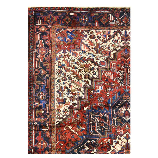 This beautiful rug is hand made, made in Iran. It features a pattern in a vibrant combination of red, blue, ivory, and...