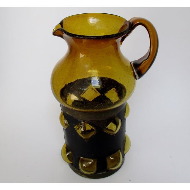 Brutalist seeded amber blown glass pitcher with a distressed metal surround that has square and diamond-shape cutouts to...