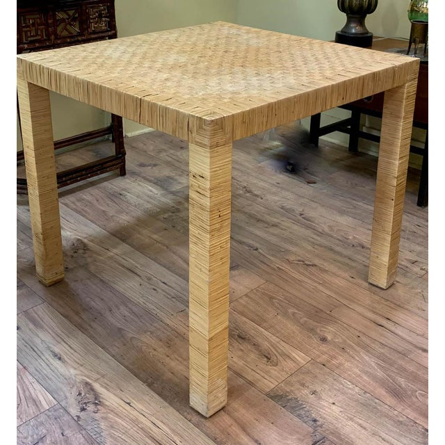 Attributed to Bielecky, maker of fine rattan and wicker furniture, this rattan basket weave dining table has the clean and...