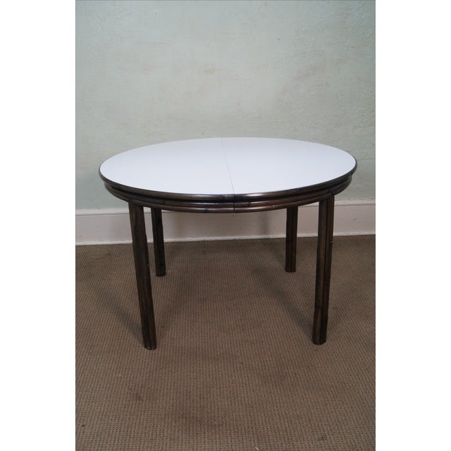 McGuire of San Francisco round bamboo rattan dining table with white laminated top. Has a table leaf. Approximately 35...