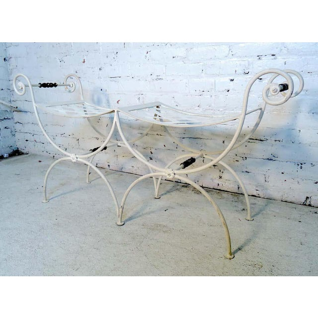 Small two seat iron bench with woven seats and scrolled arms. (Please confirm item location - NY or NJ - with dealer)....