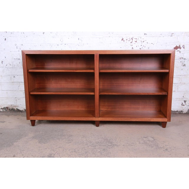 A rare and exceptional mid-century modern mahogany double bookcase designed by Edward Wormley for Dunbar Furniture. The...