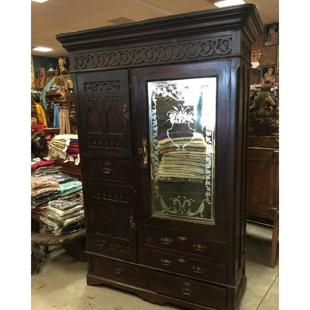A true rustic antique Armoire from Calcutta India. Wonderfully comprehensive detailed and crafted in rosewood this cabinet...