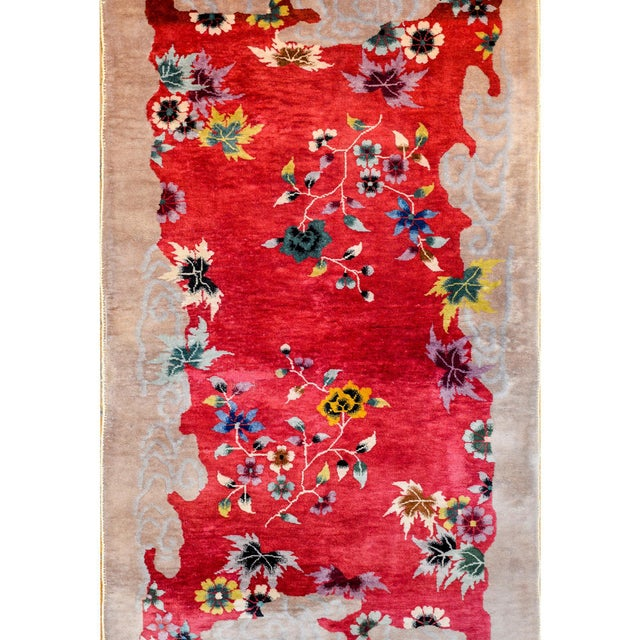An unusual Chinese Art Deco rug with a beautiful vibrant cranberry field with multicolored peonies and chrysanthemum...