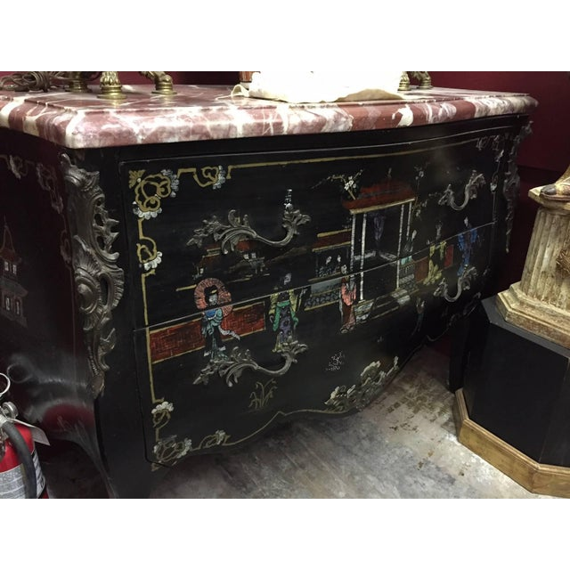 Pair of Louis XV style chinoiserie marble-topped commodes. The unusually think marble tops over ebonized bombe commodes...