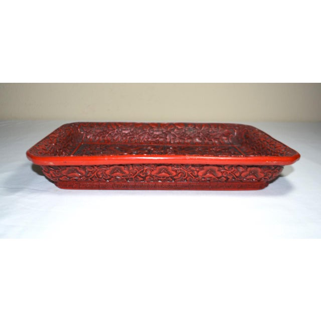 You are viewing a red cinnabar tray featuring carved serpentine-like dragons on the bottom. The bottom of the tray is...