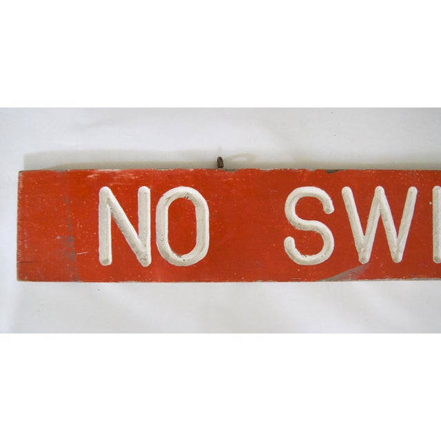 "Circa 1950's one-sided wood orange and white ""No Swimming"" sign, letters are incised. Sign has original eye hooks for..."